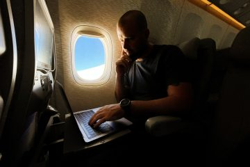 Men working on his laptop while flying in the airplane